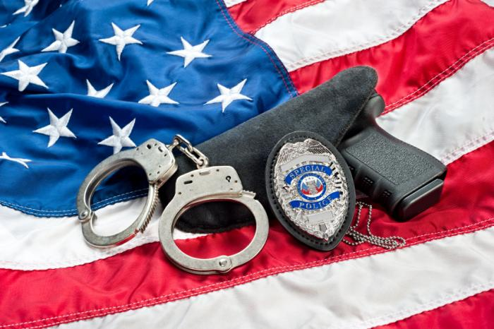 gun-with-police-badge-and-handcuffs-on-us-flag